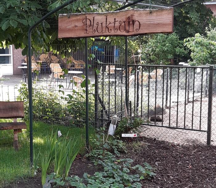 Pluktuin bij de Kadans, bordje Pluktuin, hek, planten, bankje
